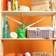Beautiful white shelves with different home related objects, on color wall background — Stock Photo #30617259
