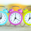 Colorful alarm clocks on table on bright background — Stock Photo
