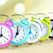 Colorful alarm clocks on table on light background — Photo