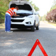 Stock Photo: Broken down car with red warning triangle