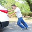 Young man pushing broken down car — Stock Photo