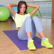 Pretty sporty girl swing press in fitness room — Stock Photo