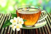 Xícara de chá com jasmim, na esteira de bambu, close-up — Fotografia Stock