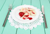 Tasty sweet dumplings with fresh strawberry on white plate, on color wooden background — Stock Photo