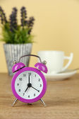 Purple alarm clock on table on beige background — Stock Photo