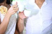 Krásný mladý romantický pár drží šálků kávy, zblízka — Stock fotografie