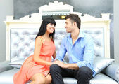 Beautiful young romantic couple sitting on sofa — Stock fotografie