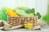 Skivad och hela råa zucchini i wicker spjällådan, utomhus — Stockfoto