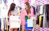 Two beautiful young woman in shop with shopping bags — Stock Photo