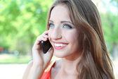 Cep telefonu yaz Park'ta konuşan güzel genç kadın — Stok fotoğraf