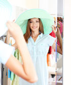 Beautiful girl trying hat near mirror on room background — Stock Photo