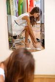 Krásná dívka snaží boty zrcadla na pozadí místnosti — Stock fotografie