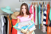 Beautiful girl with lots clothes in room background — Stock Photo