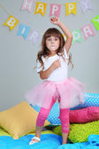Little girl dancing on bed in room on grey wall background — Stock Photo