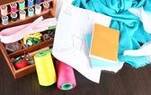 Dikiş seti ahşap kutu, kumaş ve ahşap masa üzerinde kroki — Stok fotoğraf