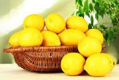 Ripe lemons in wicker basket on table on bright background — Stock Photo