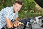 Jovem piloto reparar o motor do carro ao ar livre — Fotografia Stock