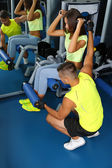 Girl and trainer engaged in simulator in gym — ストック写真