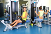 Guy and girl engaged in simulator at gym — Stock Photo