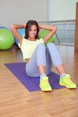 Pretty sporty girl swing press in fitness room — Stock Photo