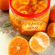 Stock Photo: Orange jam with zest and tangerines, on white wooden table