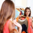 Beautiful girl trying dress near mirror on room background — Stock Photo #30673955