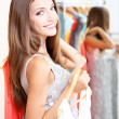 Beautiful girl with dresses near mirror  — Stockfoto