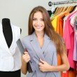 Foto Stock: Beautiful young stylist near rack with hangers