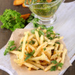 French fries on tracing paper on board on wooden table — Stock Photo #30674301