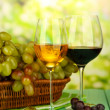 Ripe grapes in wicker basket, and two glasses of wine, on bright background — Stock Photo #30674517