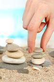Mano construye torre de piedras del mar sobre la arena en fondo luminoso — Foto de Stock