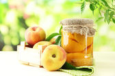 Jar of canned peaches and fresh peaches on wooden table, outside — Stock Photo