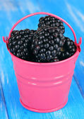 Sweet blackberries in bucket on table close-up — Stock Photo