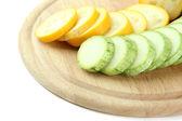 In scheiben geschnitten und ganze rohe zucchini auf holz schneidebrett, isoliert auf weiss — Stockfoto