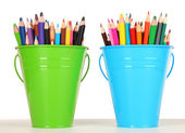 Color buckets with multicolor pencils, on color background — Stock Photo