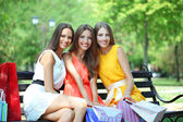 Three beautiful young woman with shopping bags in park — Stock fotografie