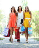 Three beautiful young woman with shopping bags in park — ストック写真