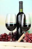 Uve mature, bottiglia e bicchieri di vino sul vassoio, su sfondo luminoso — Foto Stock