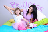 Little girl with mom on bed in room on grey wall background — Stock Photo