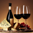 Refined still life of wine, cheese and grapes on wicker tray on wooden table on beige background — Stock Photo #30686713