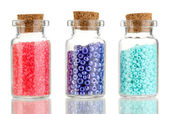 Little bottles full with colorful beads isolated on white — Stock Photo