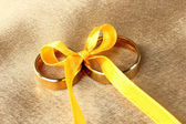 Wedding rings tied with ribbon on bright background — Stockfoto
