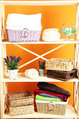 Beautiful white shelves with different home related objects, on color wall background — Foto de Stock
