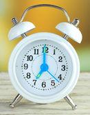 Wecker auf Tisch mit hellem Hintergrund — Stockfoto