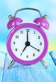 Alarm clock on table on blue background — Stock Photo