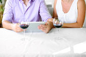 Young couple taking photo with tablet in restaurant — Stock Photo