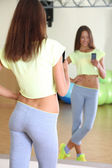 Pretty sporty girl photographing herself in mirror at phone in fitness room — Stock Photo