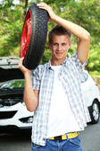 Man driver holding tire on shoulder — Stock Photo