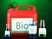 Bio fuels in canister and vials on green background — Stock Photo
