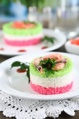 Colored rice on plates on napkin on wooden table on room background — Stockfoto